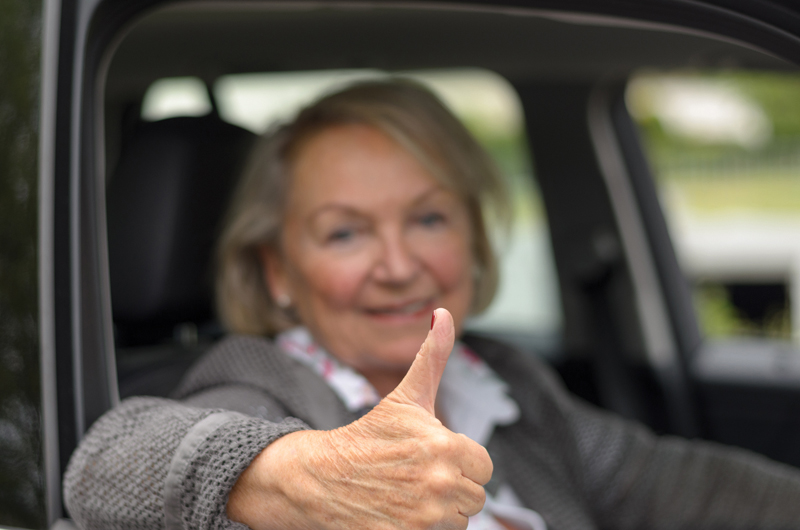 Elderly woman sitting in a car with thumb up while looking to the camera