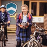 Schoolgirl with her bicycle in the school yard. Happily she holds her safety helmet as she prepares to put it on. Another student in the background can be seen riding his bike.