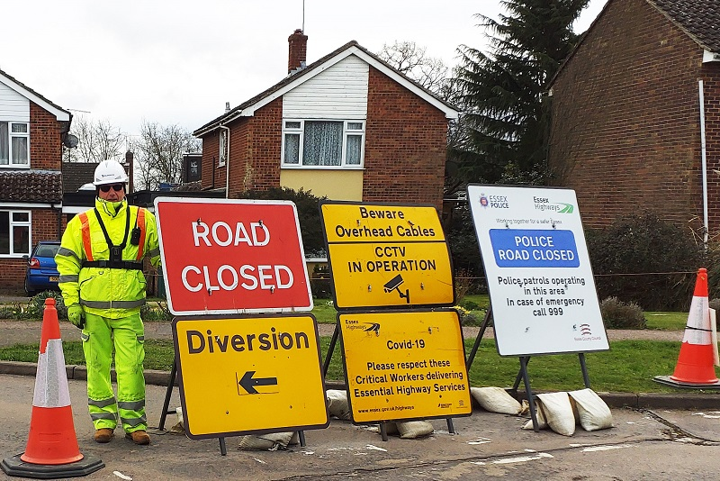 A roadworker next to some roadworks signs